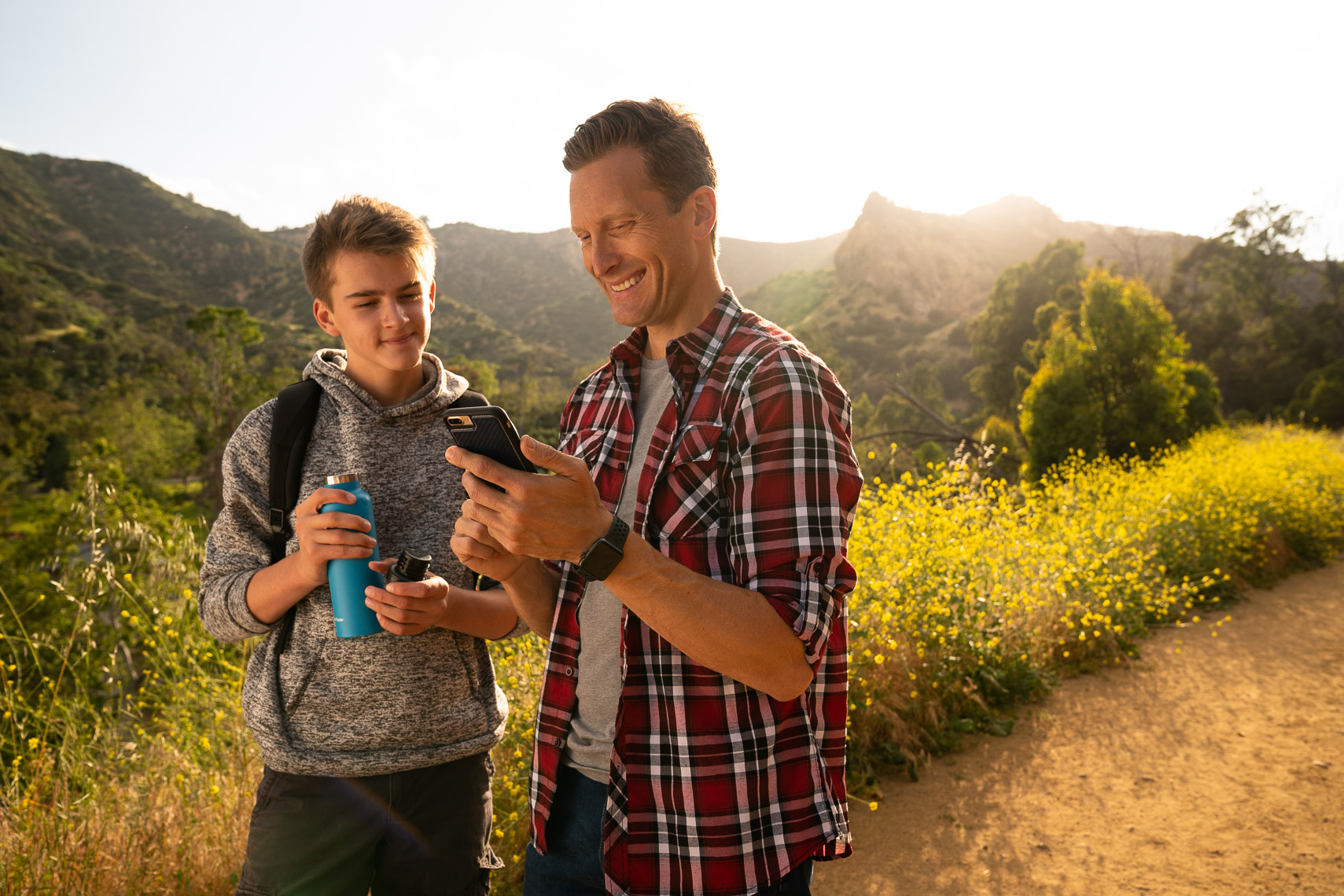 Avast - Father and Son Hiking Checking Map on Smartphone