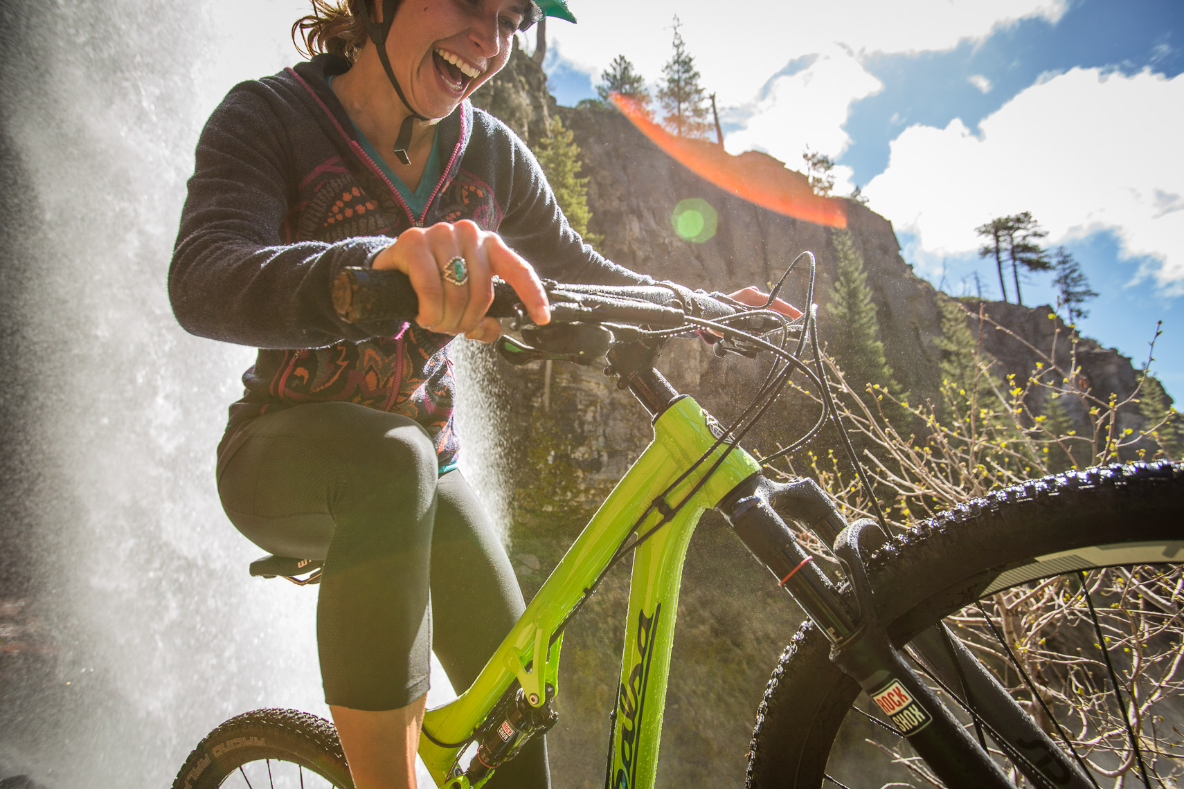 Woman Mountain Biking Near Waterfall